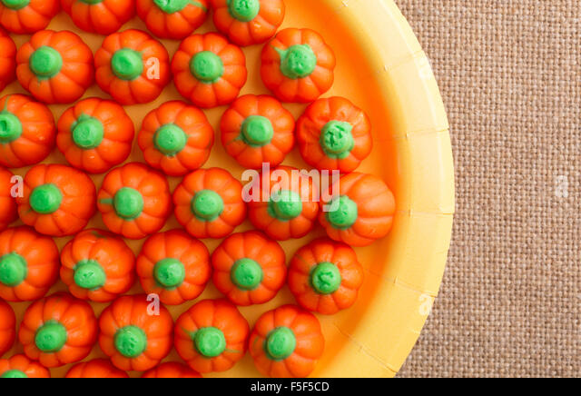 Top close view of orange and green Halloween pumpkin candy on a yellow paper plate atop a burlap tablecloth - Stock Image