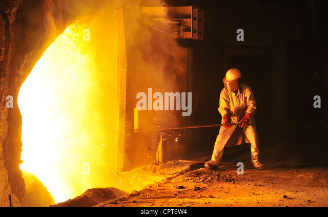 worker takes a sample at steel company - Stock Image