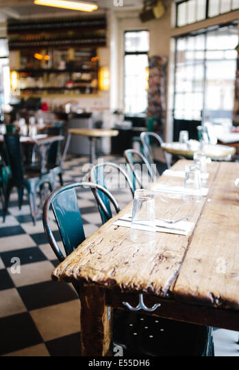 Community table with metal chairs and checkered floor in modern industrial restaurant. - Stock-Bilder