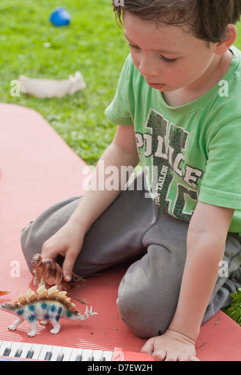 Portrait of a boy with keyboard playing outdoor in the garden. - Stock-Bilder