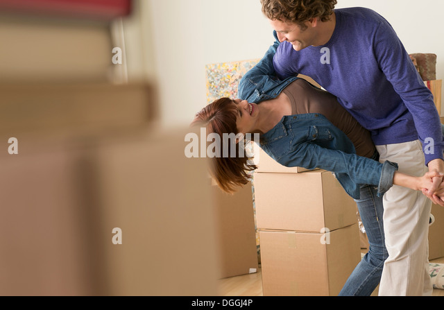 Couple dancing together whilst moving house - Stock-Bilder