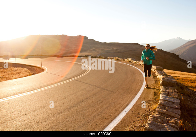 An athletic woman  runs along Trail Ridge Road (12,183 feet) near its apex at sunrise, Rocky Mountain National Park, - Stock Image