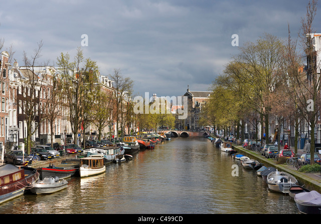 Houses and boats on a canal in early spring/late winter, Prinsengracht, Grachtengordel south, Amsterdam, Netherlands - Stock Image