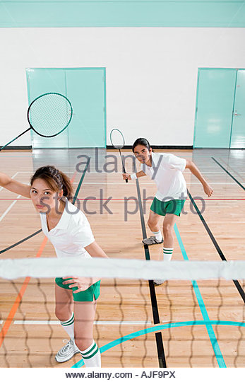 Two young people playing badminton - Stock Image