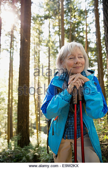 Serene senior woman hiking in sunny woods - Stock Image