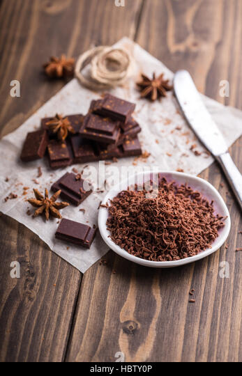 Grated dark chocolate with some pieces of chocolate on background - Stock Image