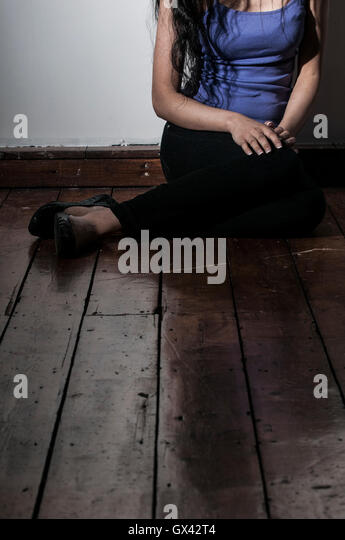 Lonely woman sat on the floor indoors - Stock Image