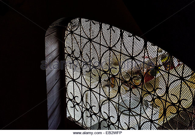 Looking through a barred and screened window into the kitchen of a home in a trading port at night. - Stock Image