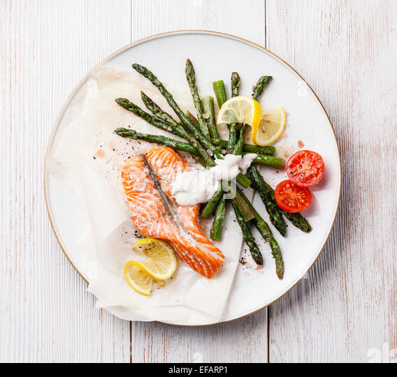 Grilled salmon with asparagus on white wooden background - Stock Image