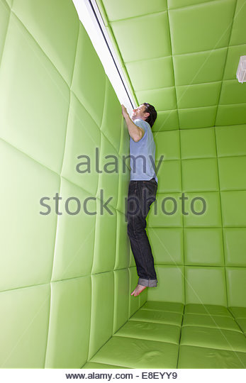 Man reaching to look out window in padded room - Stock Image