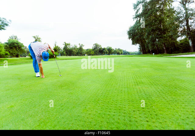 Golfer retrieving ball from the hole on a nice course - Stock Image