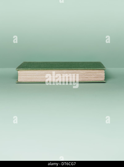 A hard cover book with a green cover, and white paper page edges, lying horizontal on a pale green background. - Stock Image