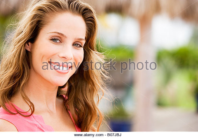 Portrait of woman with long brown hair outdoors - Stock Image