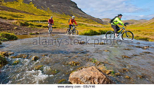 Three mountain bikers cycling through hot river, Reykjadalur valley, South West Iceland - Stock Image