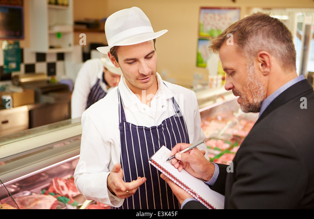 Bank Manager Meeting With Owner Of Butchers Shop - Stock Image