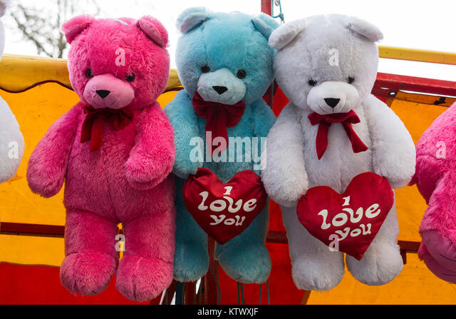 Three cuddly teddy bears, soft toys, holding an I love you heart - Stock Image