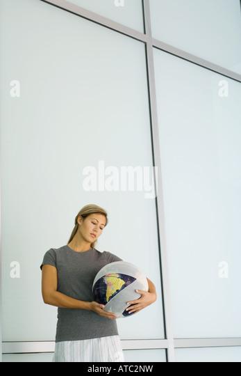 Woman holding bandaged globe - Stock Image