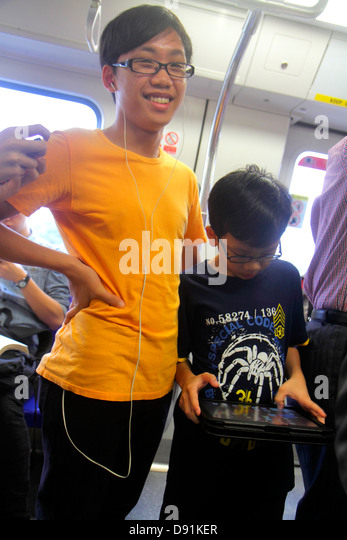 Singapore MRT North South Line subway train cabin public transportation riders commuters Asian teen boy younger - Stock Image