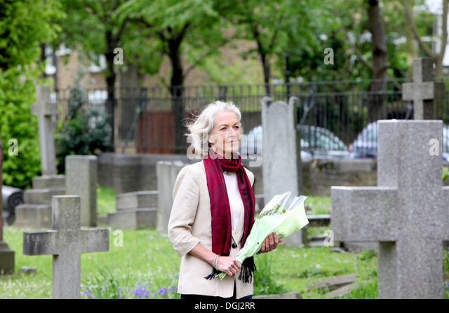 Senior woman holding flowers in graveyard - Stock Image
