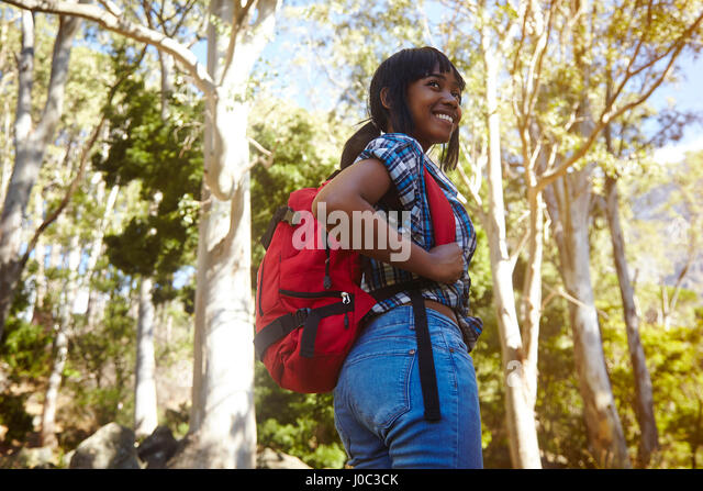 Young woman hiking through forest, looking over shoulder, smiling, Cape Town, South Africa - Stock Image