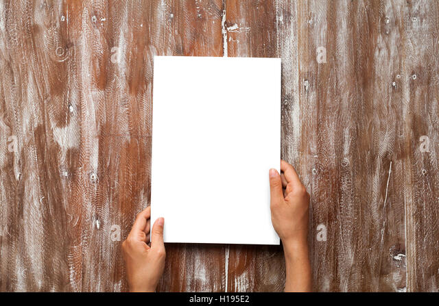 Closeup Blank White Paper Sheet Mockup Holding Male Hands Natural Wood Table Background. Empty Canvas Painted Brown - Stock Image