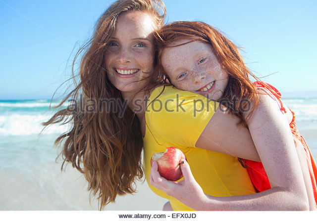 Portrait of smiling girl holding apple, embracing mother, on sunny beach - Stock Image