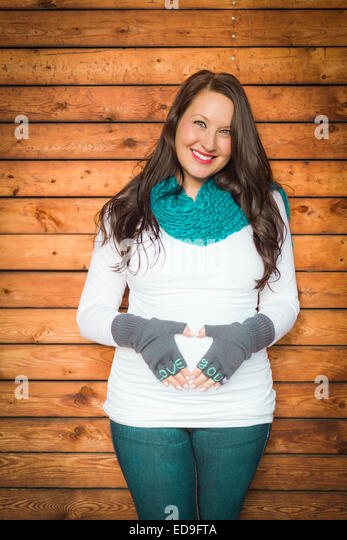 Beautiful Young Pregnant Woman Holds Her Stomach with Love You Mittens. - Stock Image