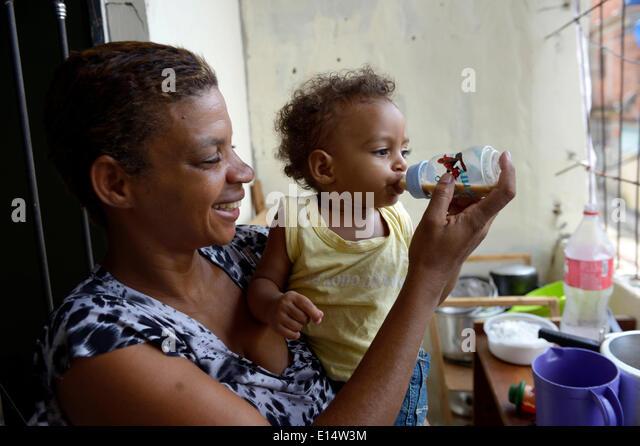 Woman, 38, in a favela, giving her son, 1 year, a bottle of drinking chocolate, Senador Camara favela, Rio de Janeiro - Stock Image