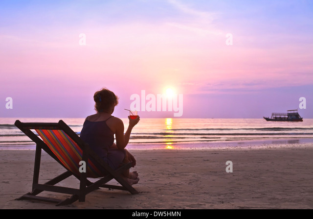 middle age woman with cocktail enjoy sunset on the beach - Stock Image