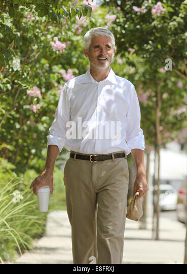 Businessman walking down street - Stock Image