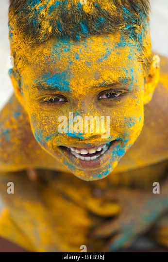 Happy young Indian boy covered in coloured powder pigment - Stock-Bilder