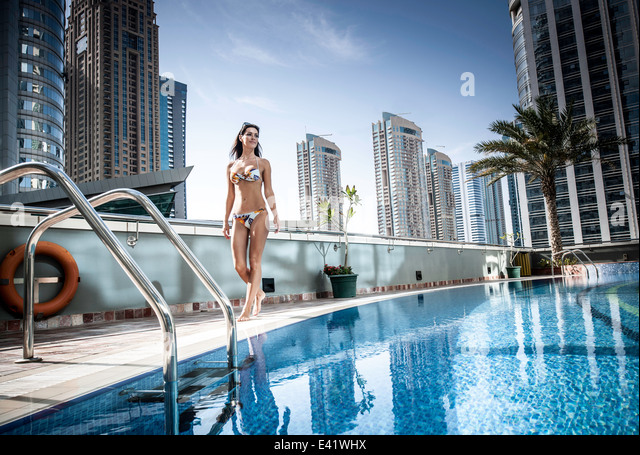 Young woman in bikini at rooftop swimming pool, Dubai, United Arab Emirates - Stock Image
