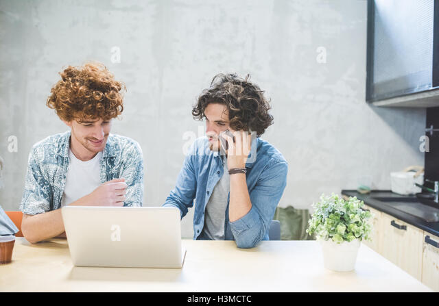 Co-workers working on laptop in office - Stock Image