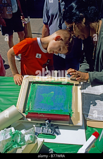 African American woman helps boy with print Earth Day Celebration Jacksonville Florida - Stock Image