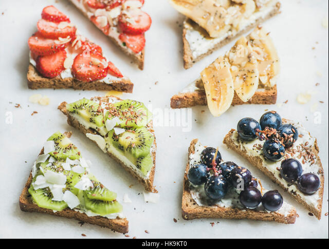Healthy breakfast wholegrain bread toasts with cream cheese, various fruit, seeds and nuts. Top view, grey marble - Stock Image