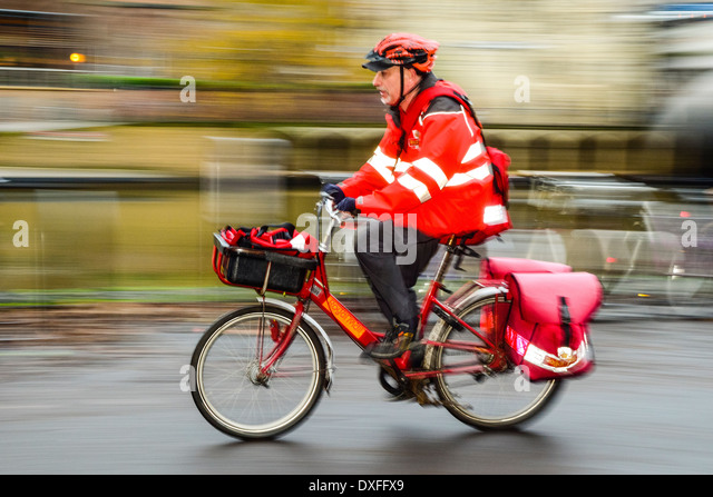 Postman on delivery bike in York Yorkshire - Stock Image