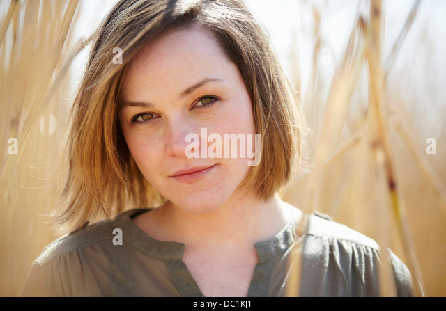 Close up portrait of young woman amongst reeds - Stock Image