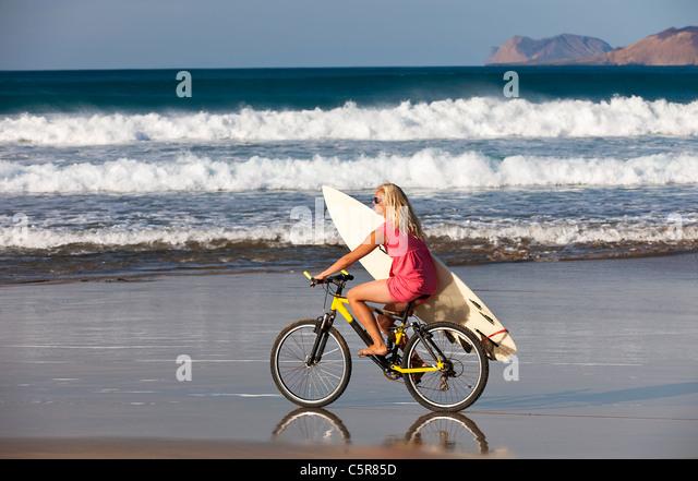 Surfer girl rides to the Ocean waves on mountain bike. - Stock-Bilder