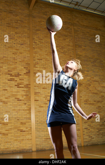 Portrait of netball player reaching for ball - Stock Image
