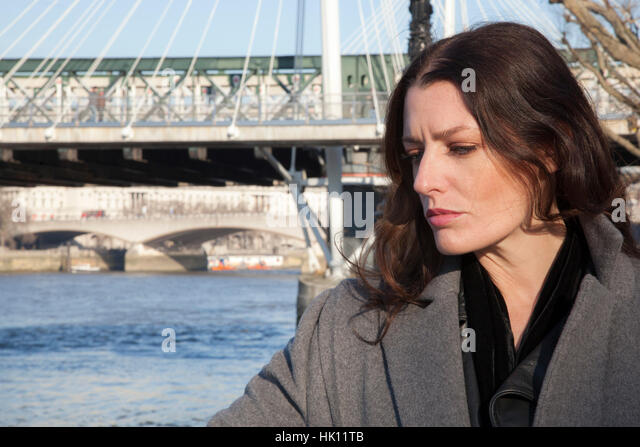 An attractive woman with long dark hair looks into the River Thames in Central London - Stock Image