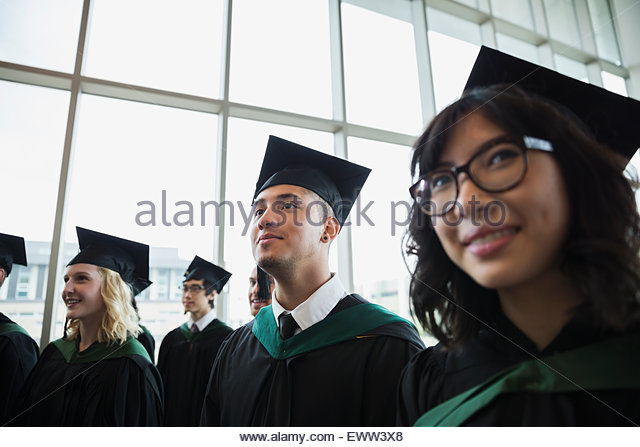 Smiling college graduates in cap and gown - Stock Image