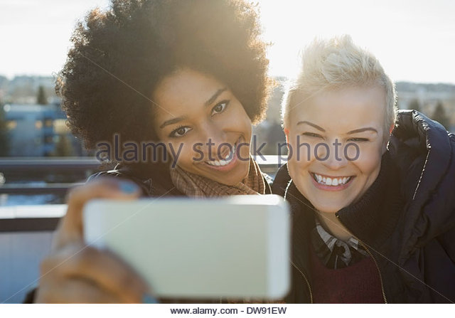 Cheerful female friends taking self-portrait outdoors - Stock Image