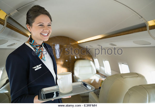 Flight attendant with coffee cup on corporate jet - Stock Image