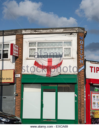 Shop fronts with flats above and St George's flag hanging out of window.  Tipton, West Midlands,, UK, October - Stock Image