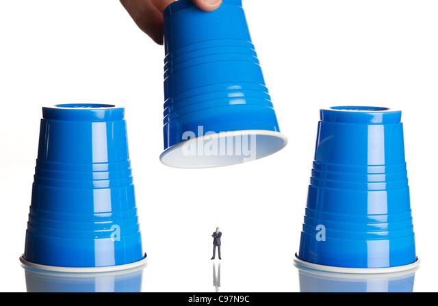 business figurines placed under plastic coffee cups - Stock Image