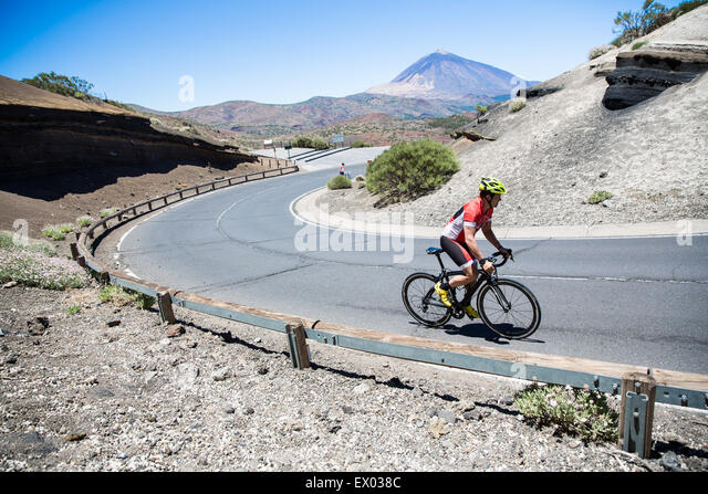 Male cyclist cycling up winding road, Tenerife, Canary Islands, Spain - Stock Image