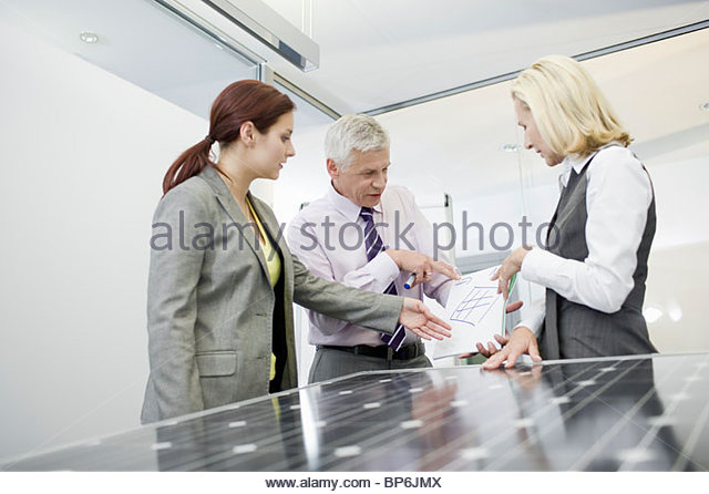 Three businesspeople discussing solar panel technology - Stock Image
