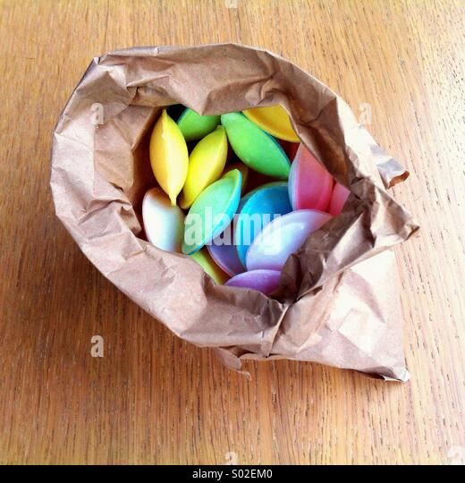 A paper bag full of colourful 'flying saucer' sweets - Stock-Bilder