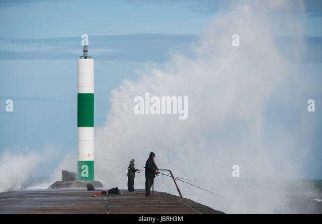 Aberystwyth Wales UK, Monday 12 June 2017 UK Weather: Fishermen cast their lines off the harbour wall as unseasonal - Stock-Bilder