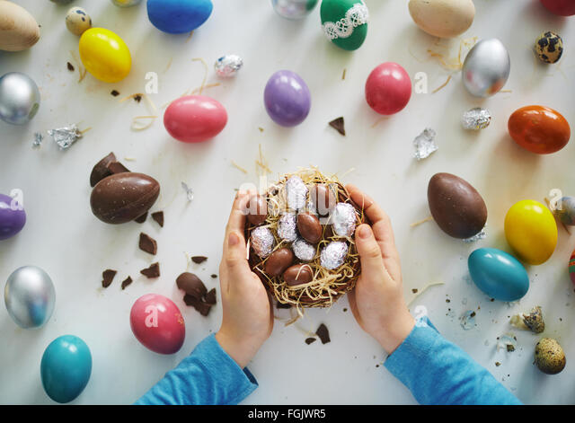 Hands of child holding small nest with chocolate eggs - Stock-Bilder